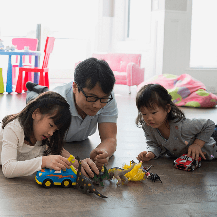 Image of father with two children playing with cars on the floor