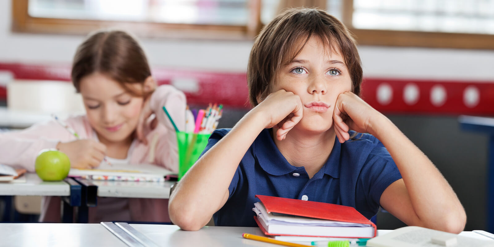 Stock image: Bored schoolboy looking away while sitting at desk with girl in background at classroom | By: Tyler Olson
